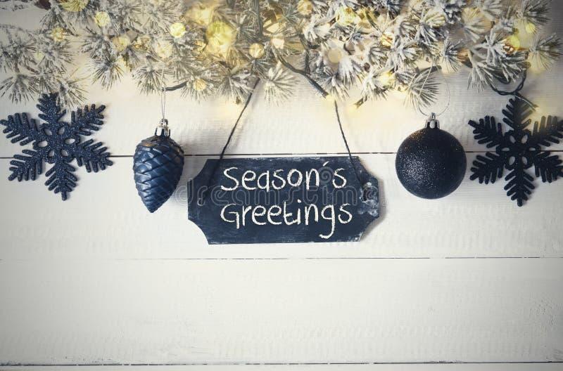 La placa negra de la Navidad, luz de hadas, texto sazona saludos imagenes de archivo