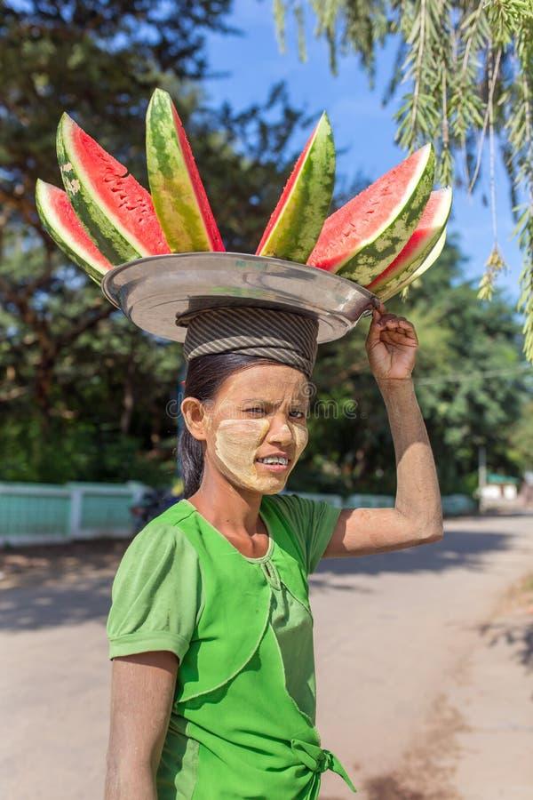 La placa que lleva de la mujer burmese no identificada con la sandía en ella va a venta en las calles de Bagan, Myanmar fotos de archivo libres de regalías