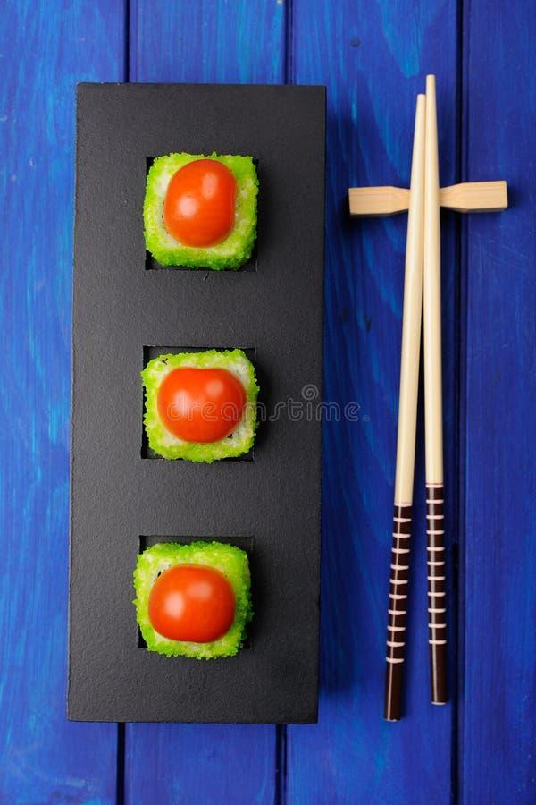 La place d'imagination roule avec la tomate et le caviar vert sur le plat noir photographie stock