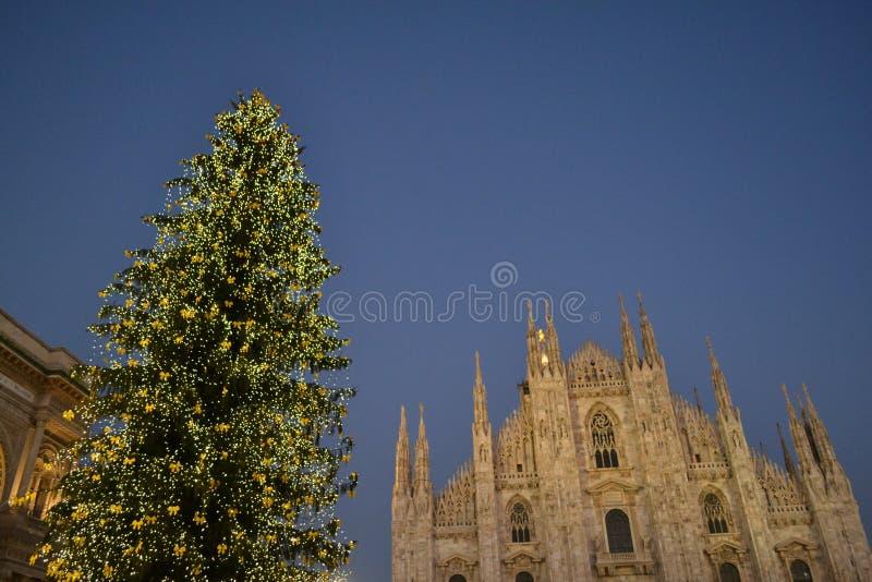 La place de Duomo de Milan a décoré de l'arbre de Noël et de la cathédrale au coucher du soleil image libre de droits