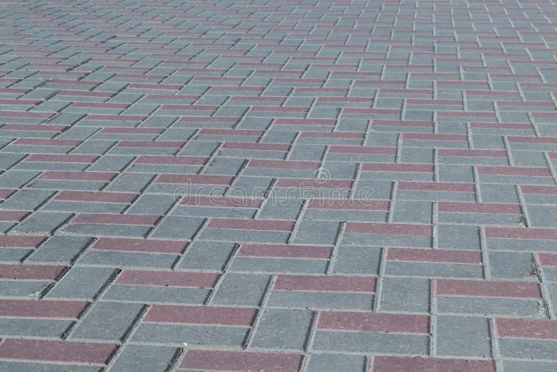 La place ou sur un trottoir a garni des tuiles brunes et grises, pavés photo stock