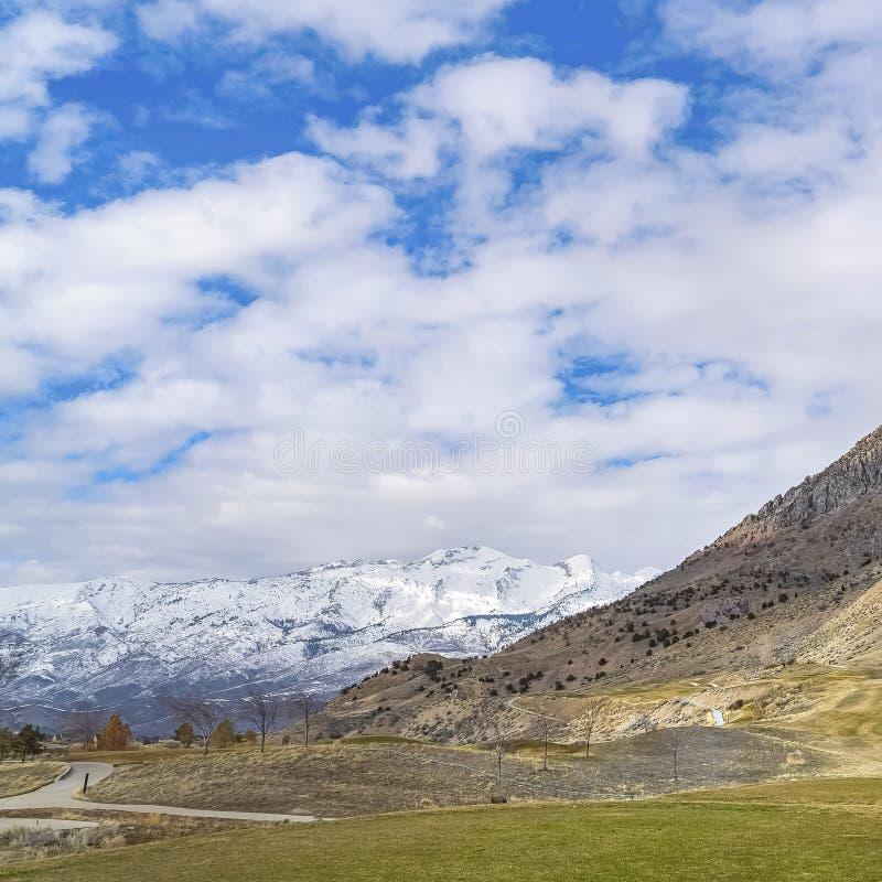 La place a pavé des routes à la base d'une montagne sous le ciel bleu vif avec les nuages gonflés image libre de droits