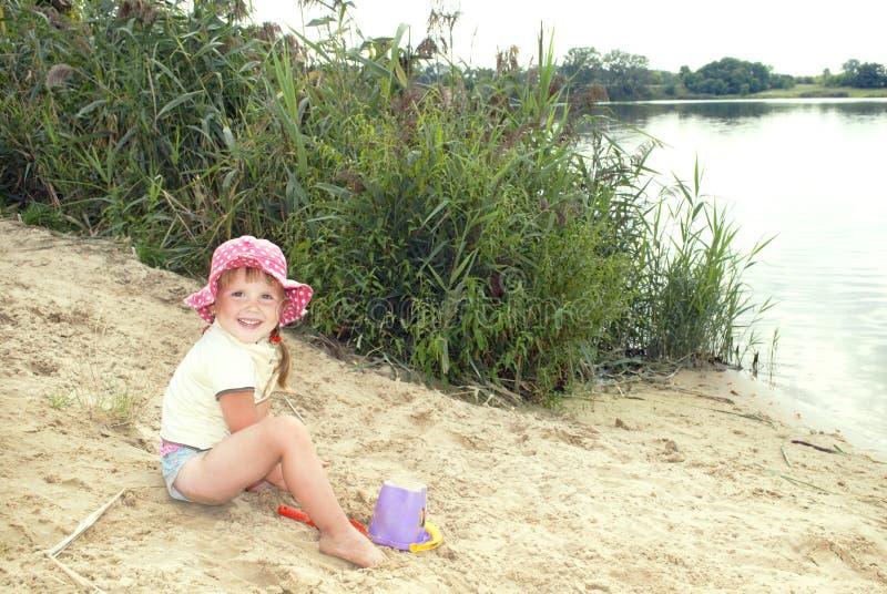 La plage au lac dans le sable une petite fille dans un playin de chapeau photographie stock libre de droits