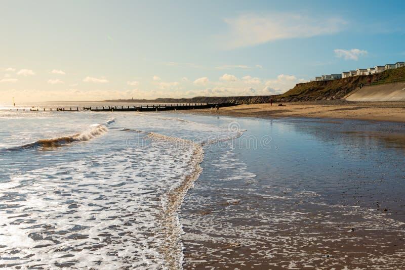 La plage de Hornsea a tiré dès l'abord un matin ensoleillé avec le parc de caravane au droit et à une marée basse vers la gauche photo libre de droits