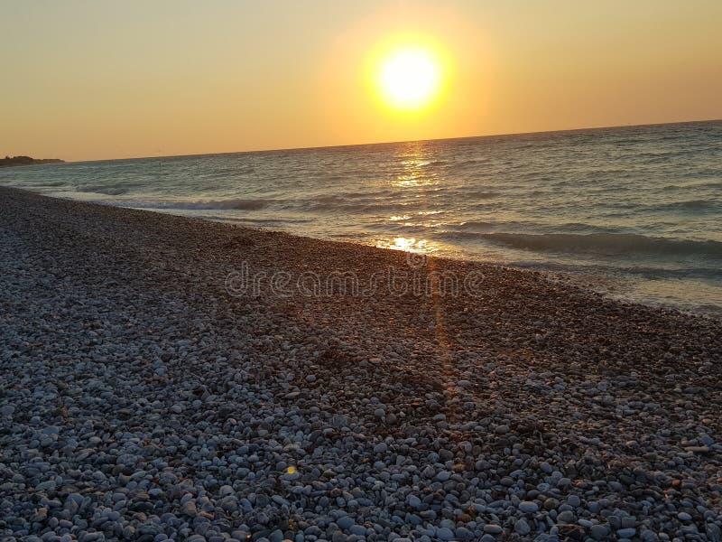 la plage de mer de coucher du soleil de Rhodes détendent des cailloux image libre de droits