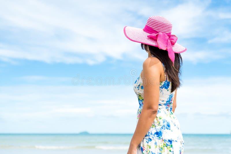 La plage et les lunettes de soleil de port de chapeau de belle femme se tiennent remet dessus la plage sablonneuse image libre de droits