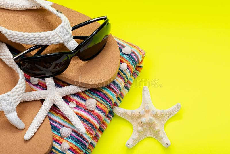 La plage Flip Flops des femmes, les serviettes de plage rayées colorées et les lunettes de soleil noires décorées des étoiles de  photo libre de droits