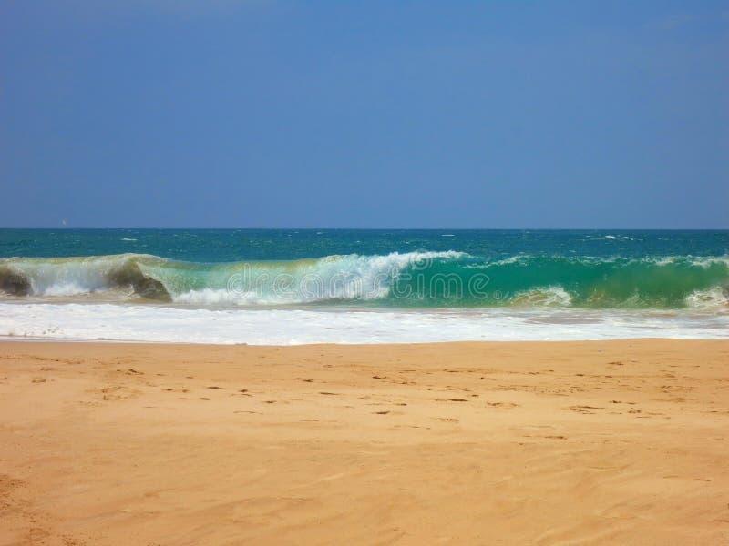 La plage vide d'océan avec le sable et le bleu clairs jaunes ondule image libre de droits