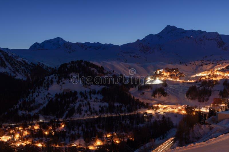 La Plagne skidar semesterorten i franska savojkålfjällängar på skymning i vinter Sikten av snö täckte berg och byggnader arkivbilder