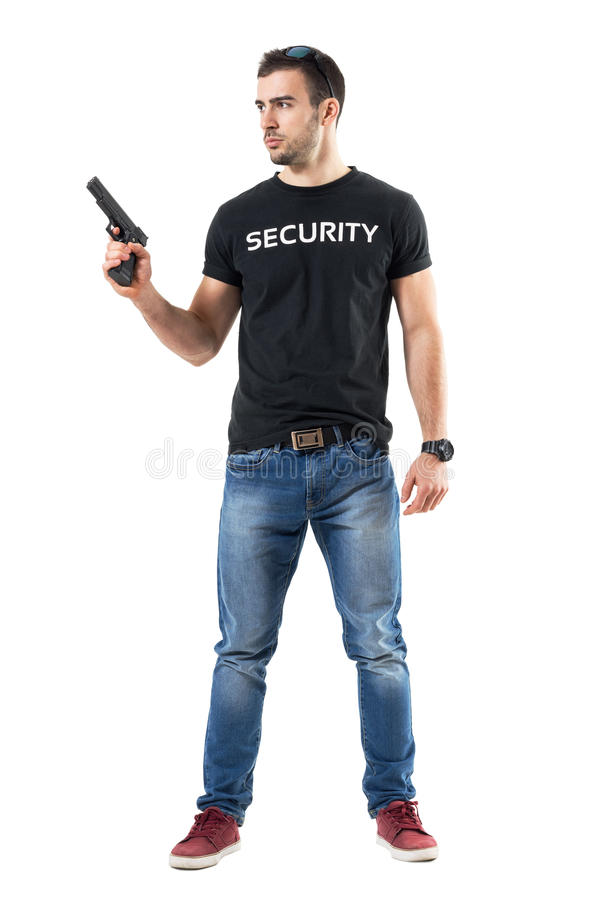 La plaine prudente alertée vêtx le policier tenant l'arme à feu regardant loin photo stock