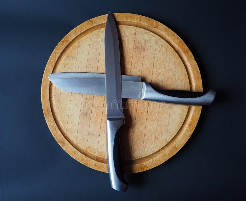 La planche à découper en bois ronde avec deux a croisé des couteaux images stock