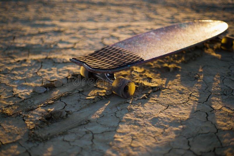 La planche à roulettes ou le longboard a collé dans le sable dans le désert au coucher du soleil photo libre de droits
