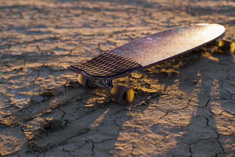 La planche à roulettes ou le longboard a collé dans le sable dans le désert au coucher du soleil photo stock