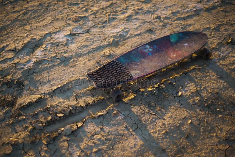 La planche à roulettes ou le longboard a collé dans le sable dans le désert au coucher du soleil images stock