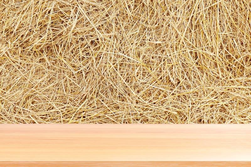 La planche en bois sur la paille, les planchers en bois vides de table sur la paille font les foins le fond sec, contexte avant v photo libre de droits