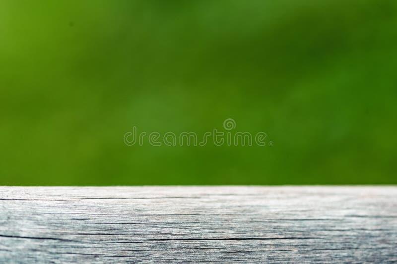 La plancia di legno vuota con la luce verde del bokeh del fondo della natura della sfuocatura, l'insegna o l'intestazione per ann fotografia stock
