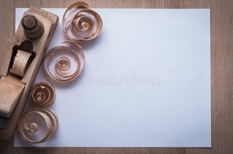 La planeuse en bois a courbé les scobs et la page du papier blanche sur le verrat en bois images stock
