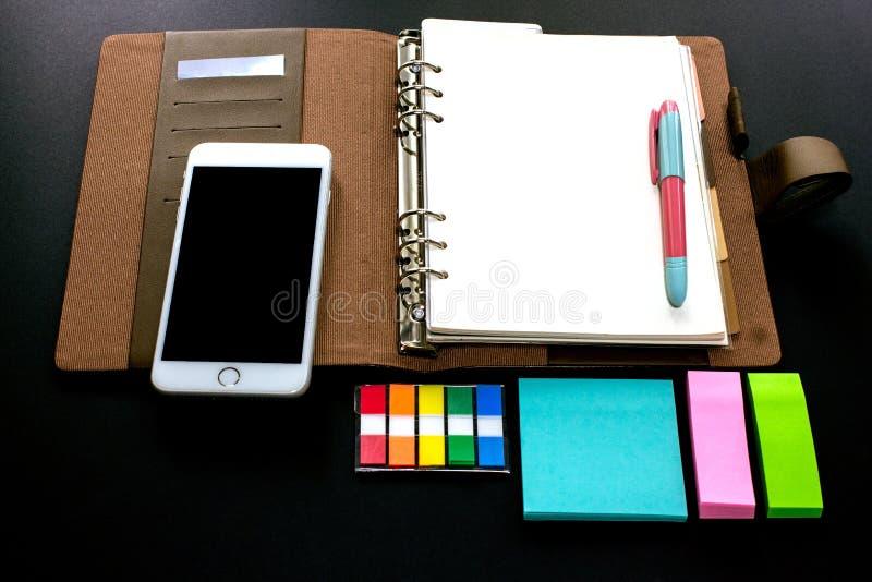 La planificatrice vide de reliure à anneaux avec des étiquettes d'index, le téléphone portable et les blocs-notes emploient pour  images libres de droits