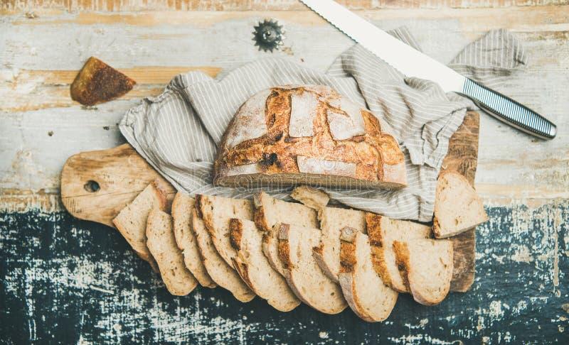 la Plano-endecha del pan del trigo del pan amargo cortó en rebanadas en la tabla imagenes de archivo