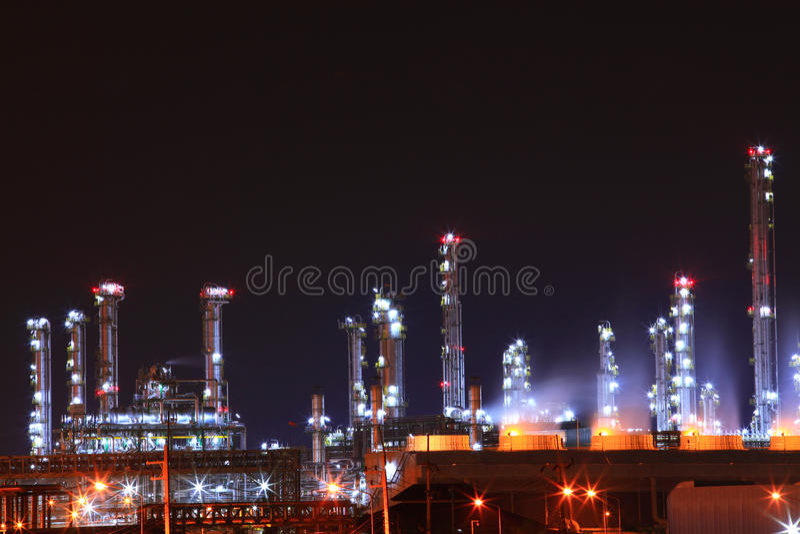 La planta petroquímica de la refinería de petróleo brilla en la noche, fotos de archivo