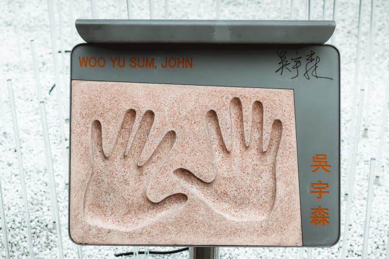 La plaque avec l'empreinte de main du cinéaste chinois légendaire John Woo d'action a placé dans le jardin des étoiles en Hong Ko image stock