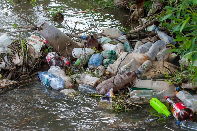 La plastica di galleggiamento imbottiglia il piccolo fiume immagine stock
