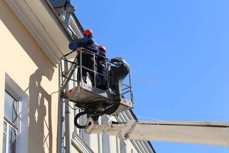 La plataforma de elevación con los trabajadores contra el cielo azul, constructores está reparando el canal del tejado imagen de archivo