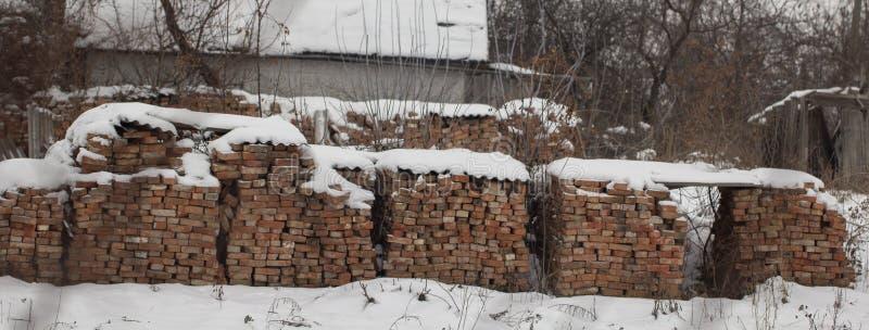 la plataforma de madera del almacén al aire libre de los ladrillos rojos cubrió nieve en otra tal plataforma imagenes de archivo