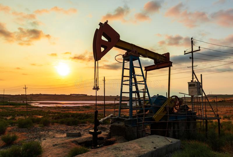 La plataforma petrolera bombea en contra de un cielo colorido de la puesta del sol foto de archivo libre de regalías
