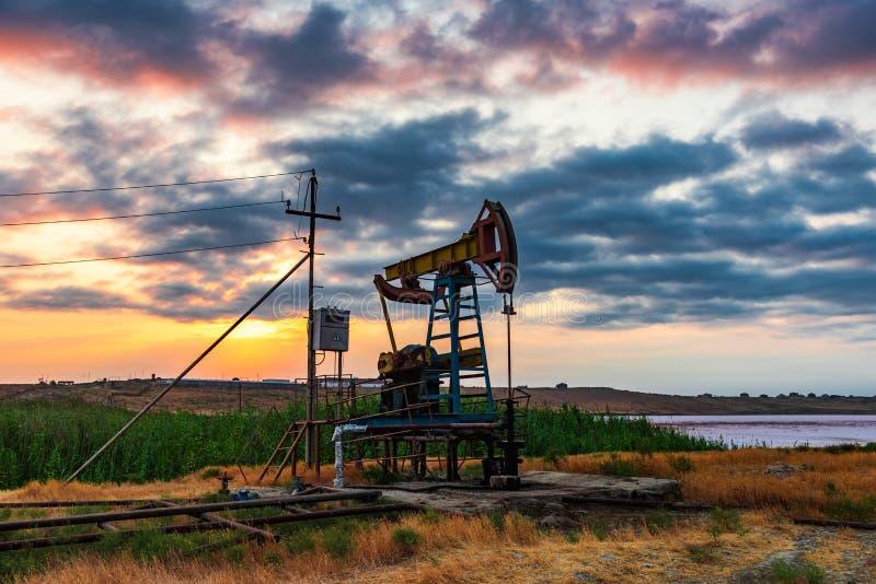 La plataforma petrolera bombea en contra de un cielo colorido de la puesta del sol fotografía de archivo libre de regalías
