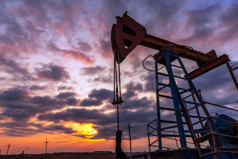 La plataforma petrolera bombea en contra de un cielo colorido de la puesta del sol imagen de archivo