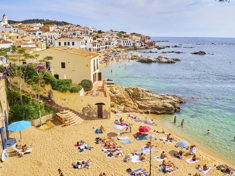 La Platgeta de Calella, a little beach of Calella de Palafrugell. Spain. Calella de Palafrugell, Spain - September 15, 2018. Tourists enjoying a sunbathing in La royalty free stock photo