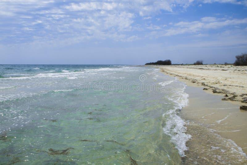 La playa abandonada del cuento de hadas con la arena de oro, el cielo hermoso y la turquesa riegan en las orillas del océano imagen de archivo libre de regalías