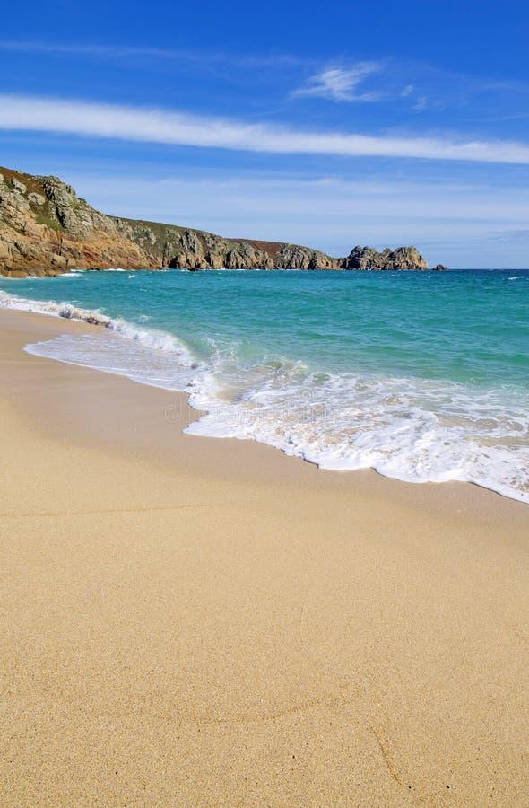 La playa arenosa y Logan de Porthcurno oscilan en Cornualles Inglaterra imágenes de archivo libres de regalías