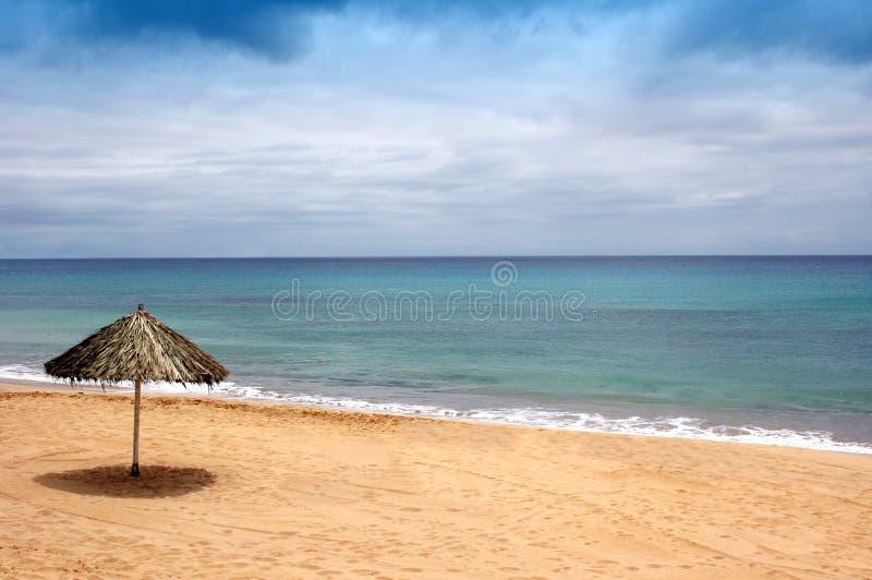 La playa de enarena con el sombrero del sol imagen de archivo