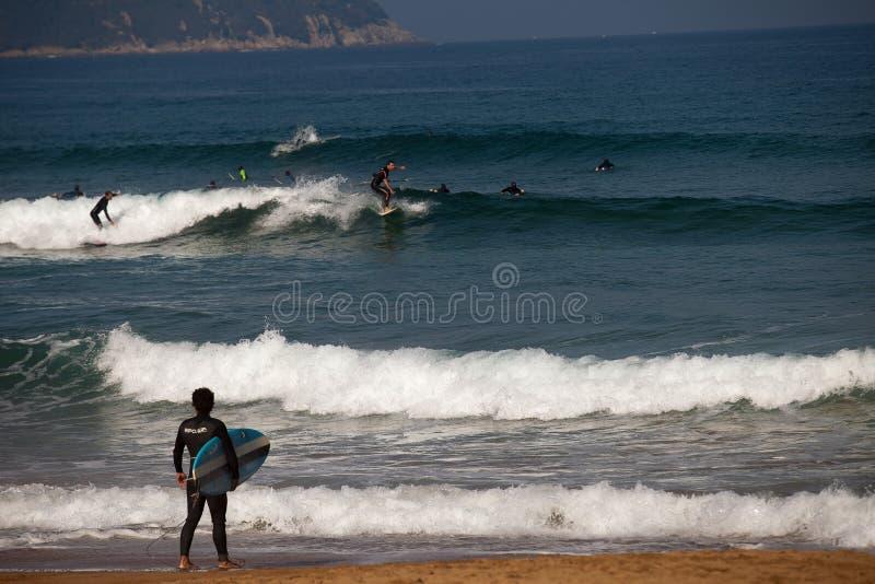 La playa de la persona que practica surf de Zarautz con una ejecución del tablero viste imágenes de archivo libres de regalías