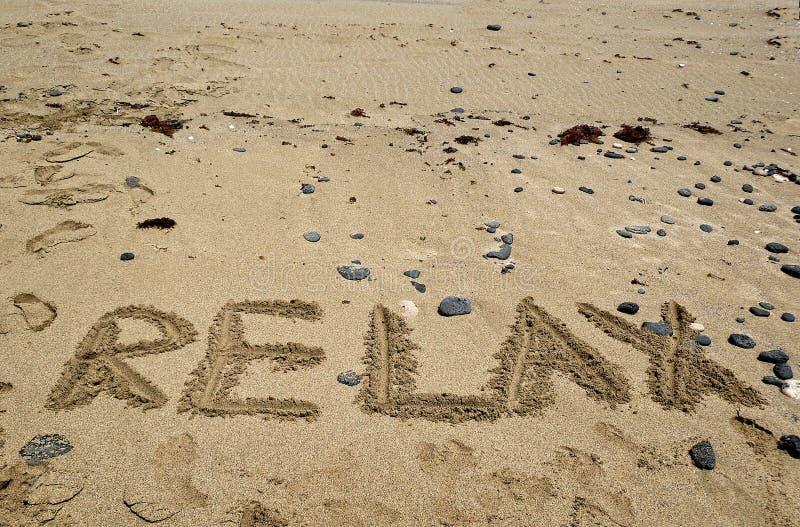La playa de Sandy y el fondo de los días de fiesta con la palabra SE RELAJAN fotos de archivo libres de regalías