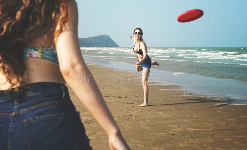 La playa del disco volador de la costa de las mujeres de la mujer de la muchacha relaja concepto fotos de archivo