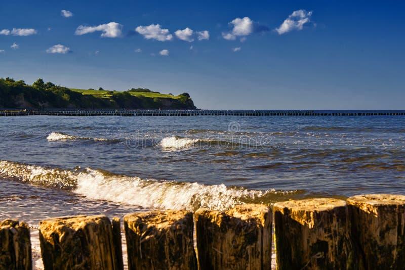 La playa del Mar Báltico en plena ebullición. Hay rompeolas de madera y en la playa de arena hay numerosas pequeñas fotografía de archivo