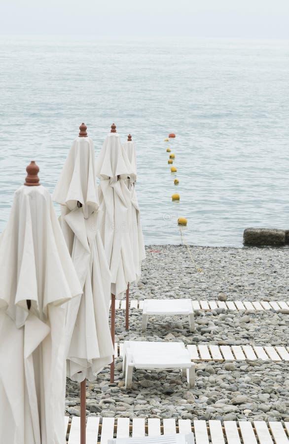 La playa del mar, guijarros, paraguas, sunbed, acceso al mar Resto o imágenes de archivo libres de regalías