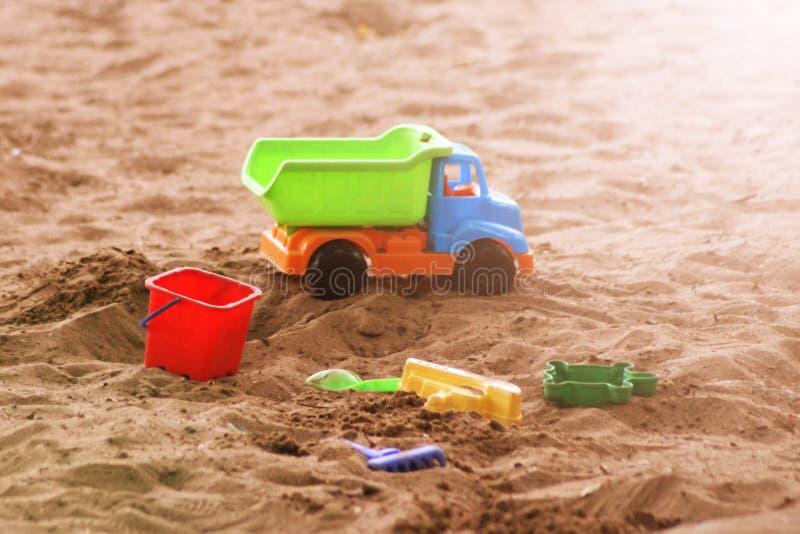 La playa del ` s de los niños juega - los cubos, la pista y la pala en la arena en un día soleado fotografía de archivo