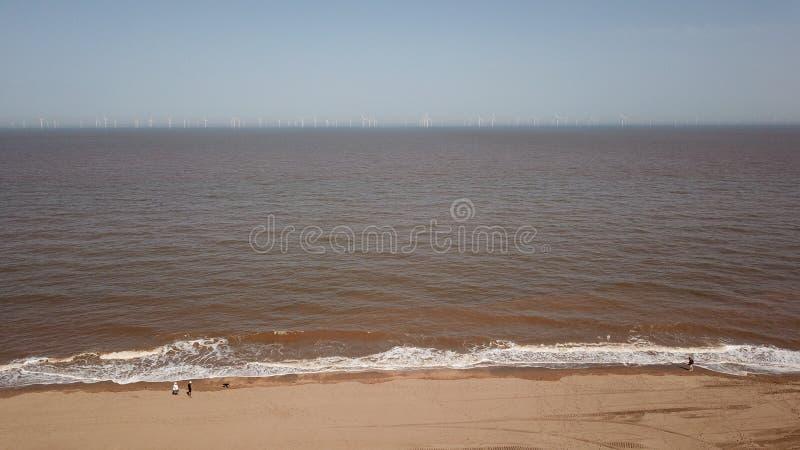 La playa, línea Inglaterra de la costa, de la energía eólica del verde de la orilla, windfarm, abejón verde de la energía tiró ai foto de archivo