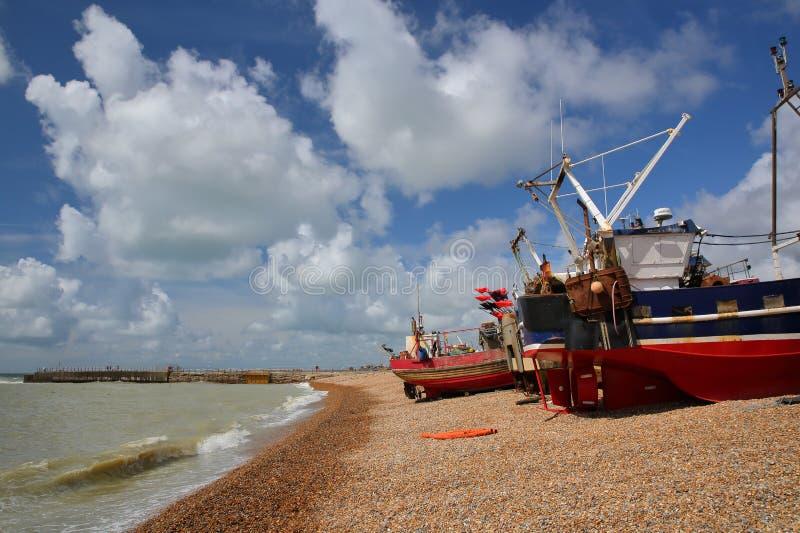 La playa lanzó los barcos de pesca con un cielo hermoso, Hastings, Reino Unido imagen de archivo