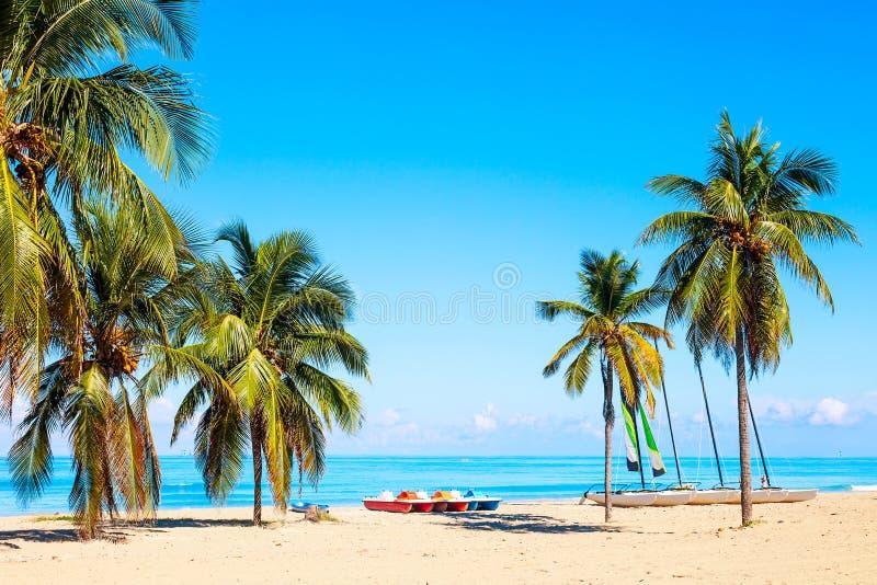 La playa tropical de Varadero en Cuba con los veleros y las palmeras en un d?a de verano con agua de la turquesa Fondo de las vac fotos de archivo libres de regalías