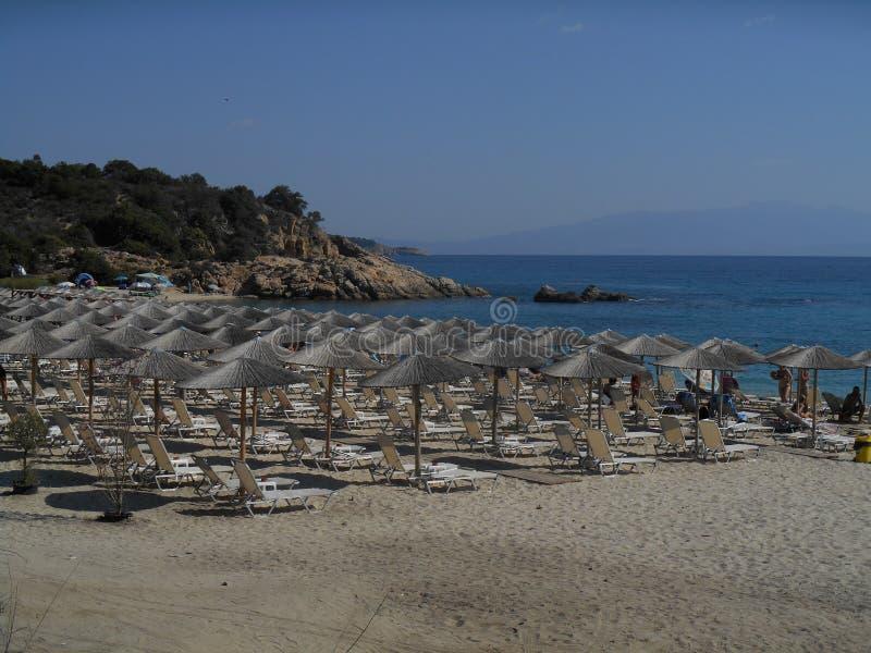 La playa y los parasoles acercan al mar fotos de archivo