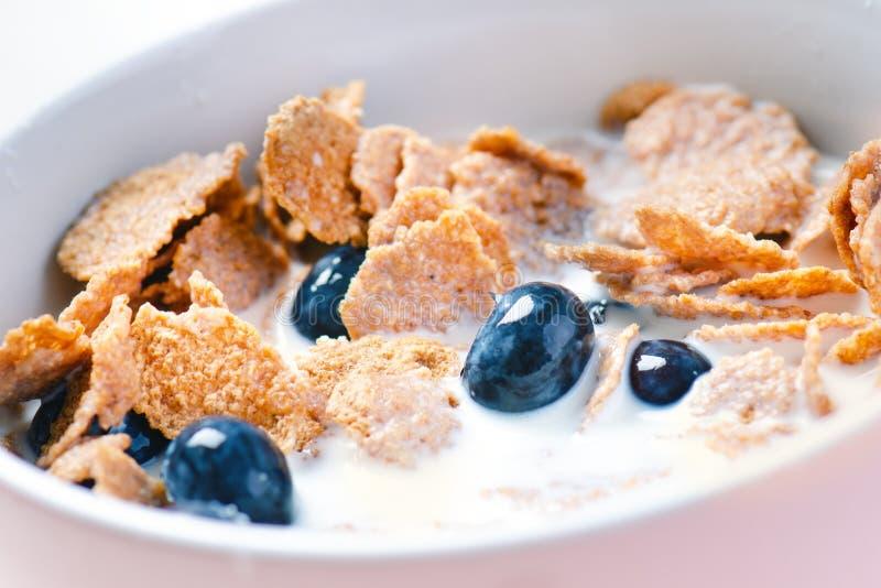 La pleine cuvette de muesli sur une table blanche avec la myrtille et le lait éclaboussent Céréales de petit déjeuner saines avec photo libre de droits