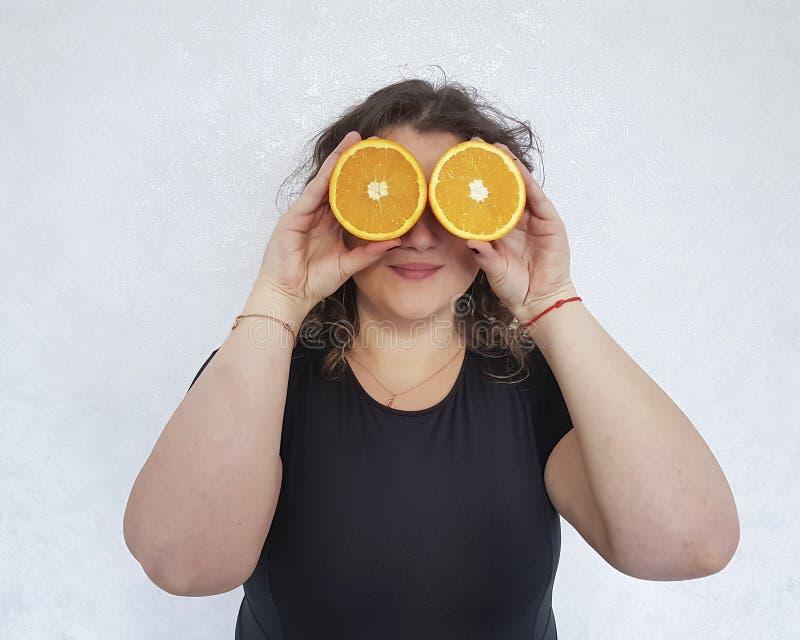 La pleine fille, une orange se tient près du régime heureux de tranche de yeux photos stock
