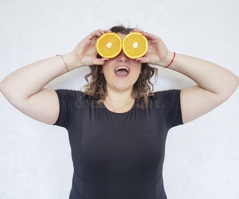 La pleine fille, une orange se tient près du régime heureux de tranche de yeux de jus images libres de droits