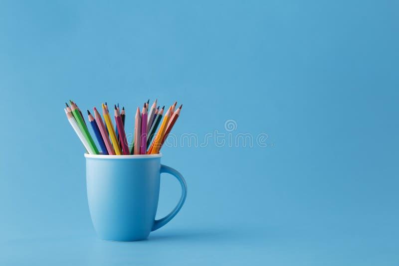 La pleine tasse de couleur pointue crayonne sur le fond bleu monochromatique photo libre de droits