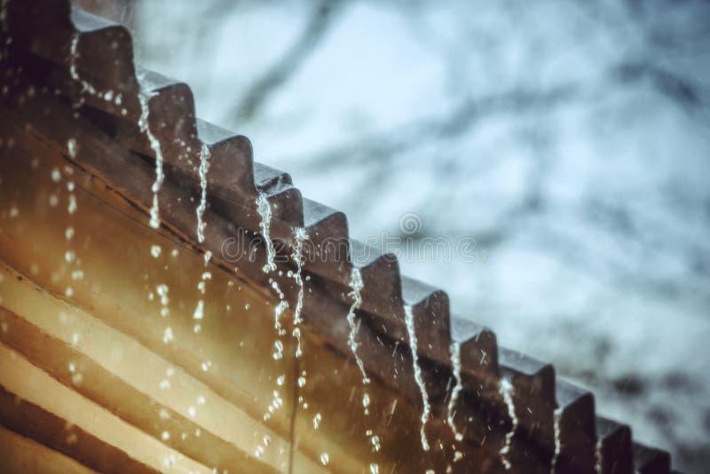 La pluie coule vers le bas d'un toit vers le bas images libres de droits
